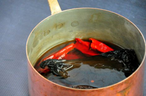 After toasting the chile peppers in a pan, let them soak in water to soften them up a bit...